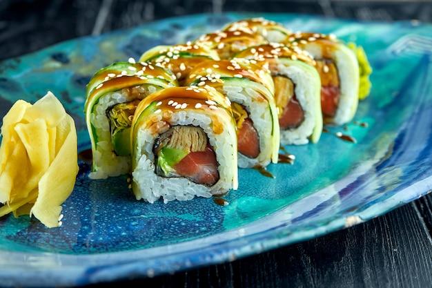 Rouleaux de sushis japonais frais avec concombre, sauce unagi et saumon, servis dans une assiette bleue sur une surface sombre. cuisine japonaise