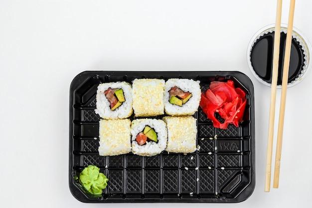 Rouleaux de syake dans un ensemble de 6 pièces dans une boîte noire, avec gingembre, wasabi et sauce soja, restauration rapide, orientation horizontale, vue de dessus