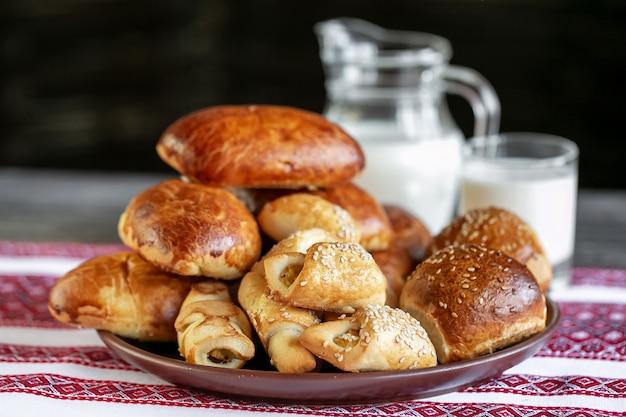 Rouleaux de viande et brioches sur une table avec du lait en arrière-plan. petits pains au four fourrés à la viande.
