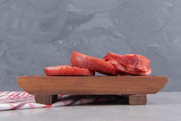 Rouleaux de viande fumée sur planche de bois.