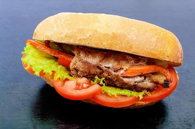 Rouleaux de viande sandwich aux légumes dans un petit pain avec des feuilles de tomate et de laitue