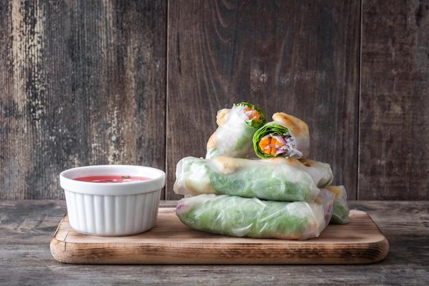 Rouleaux vietnamiens avec légumes, nouilles au riz et crevettes sur bois