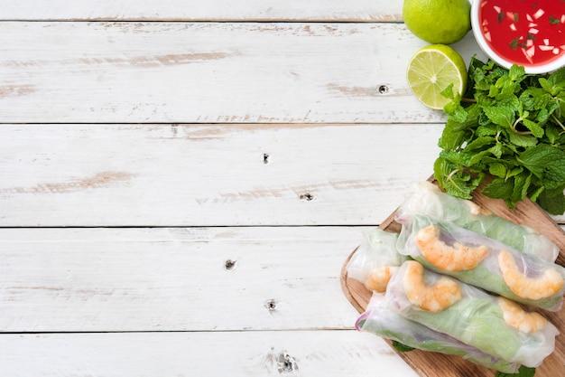Rouleaux vietnamiens avec légumes, nouilles au riz et crevettes à la sauce chili douce sur bois blanc. vue de dessus. fond