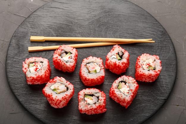 Rouler aux crevettes et au caviar tobiko et bâtonnets sur une planche ronde noire sur fond gris. copier l'espace photo horizontale