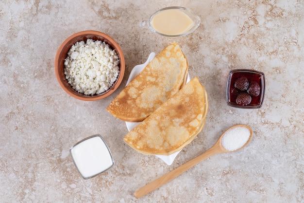 Rouler les crêpes au fromage cottage et à la confiture de fraises
