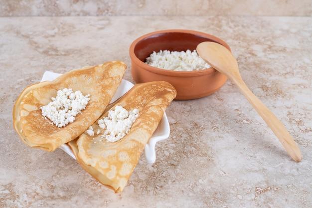 Rouler les crêpes avec du fromage cottage et une cuillère en bois
