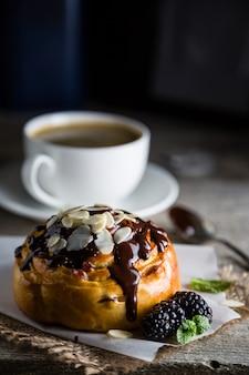 Rouler avec du chocolat, des noix et des baies, table en pierre sombre