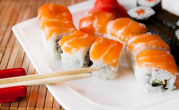 Rouler avec du fromage à la crème et du concombre à l'intérieur. saumon garni