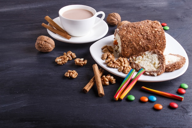 Rouler le gâteau au caillé et aux noix isolé sur bois noir