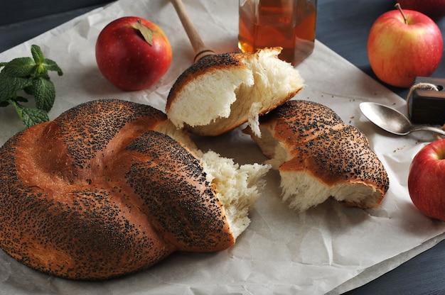 Rouler avec des graines de pavot, déchirées en morceaux gros plan de pommes, menthe et miel