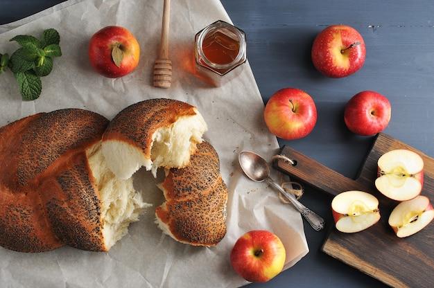 Rouler avec des graines de pavot, déchirés en morceaux gros plan - pommes et miel