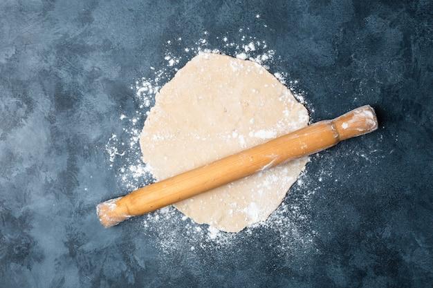 Rouler la pâte sur une table avec un rouleau à pâtisserie en bois.