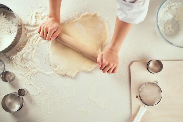 Rouler la pâte sur le travail de cuisine de produits de farine de table