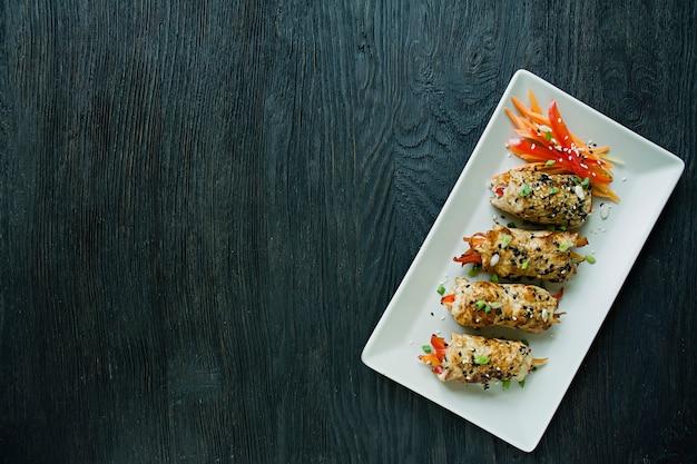Rouler avec une poitrine de poulet fraîche avec des légumes verts, des tranches de carotte, des poivrons sur une planche à découper sombre.