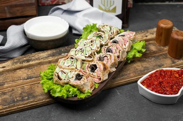 Rouler la salade dans du pain lavash sur une feuille de laitue servie avec de la pâte de tomate