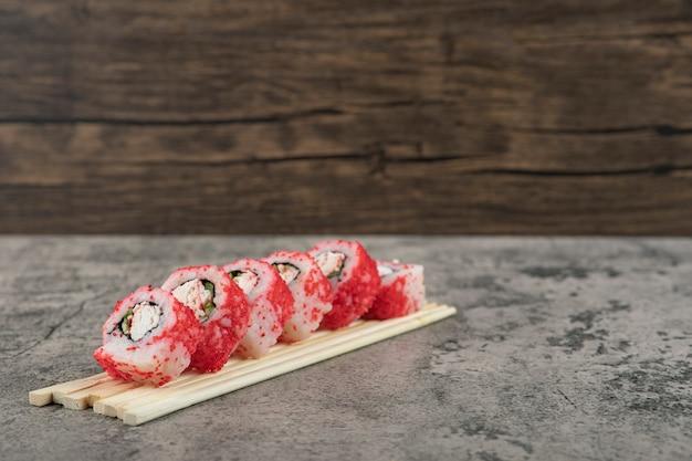 Rouler les sushis avec des baguettes sur un fond de pierre.