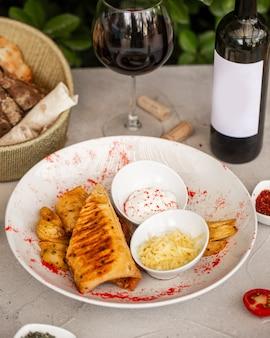 Roulés frits servis avec pommes de terre, fromage râpé et mayonnaise