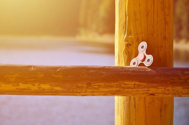 Une roulette en bois se trouve sur une barre en bois sur fond d'eau de rivière