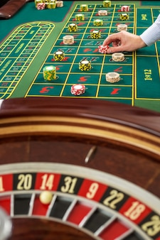 Roulette et piles de jetons de jeu sur une table verte