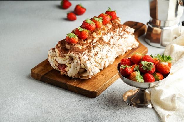 Roullade de meringue: rouler avec de la crème et des fraises fraîches