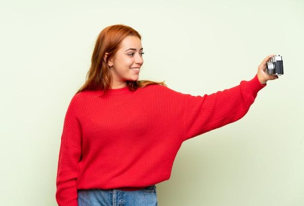 Rousse adolescente avec pull sur mur vert isolé faisant un selfie