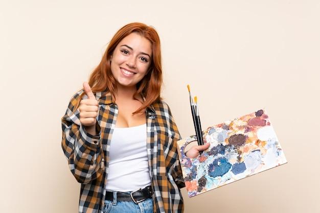 Rousse adolescente tenant une palette isolée donnant un geste du pouce