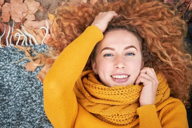 Rousse bouclée belle femme allongée sur les feuilles d'automne