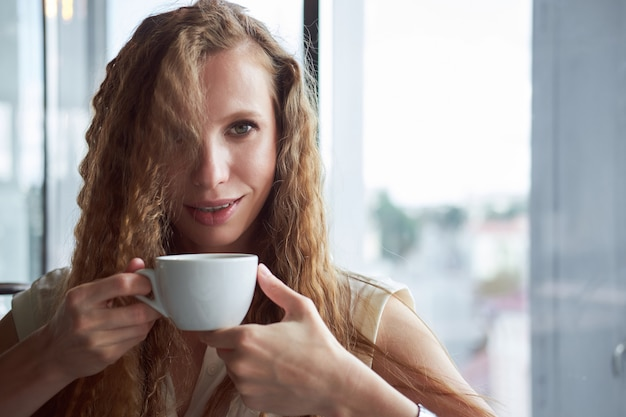 Rousse bouclée fille maigre blanche en chemise blanche, boire du café et souriant