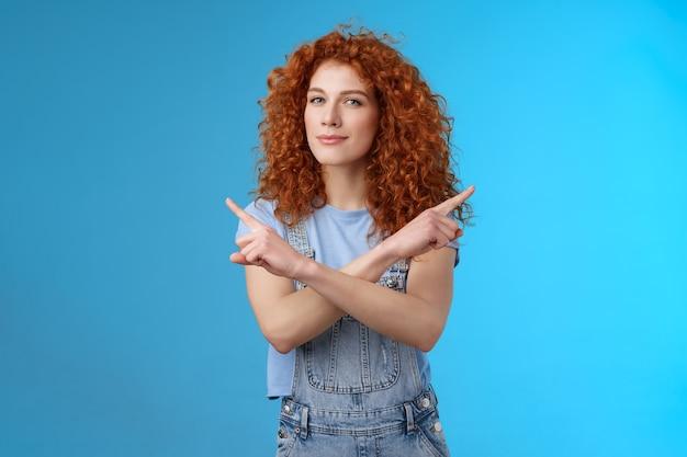 Rousse créative curieuse attrayante jeune femme moderne aux cheveux bouclés, intriguée, pointant sur le côté, gauche, droite, louchant la caméra, demandant des conseils, faisant le choix de décider quel produit fond bleu.