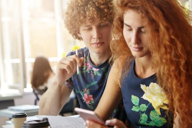 Rousse femme et homme assis ensemble entouré de cahiers