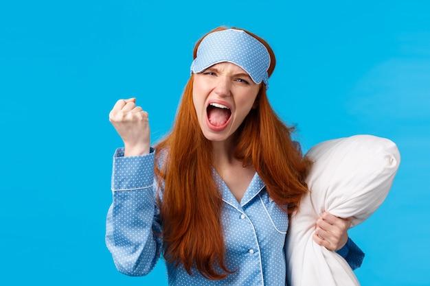 Rousse folle, outragée et furieuse, caucasienne, criant, maudissant le colocataire étant trop fort la nuit, ne peux pas dormir, serrant le poing en colère, fronçant les sourcils, tenant un oreiller, portant un masque et des vêtements de nuit