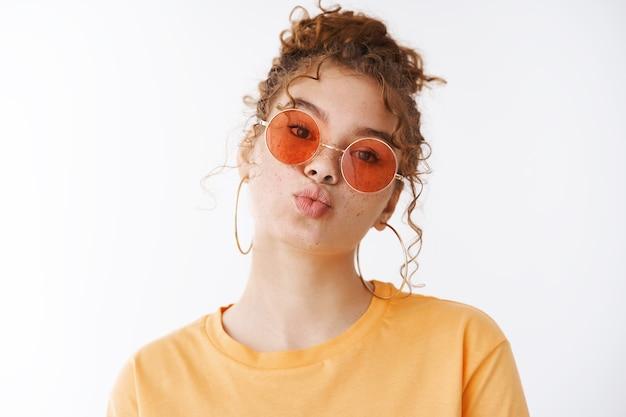 Rousse glamour chic et idiote jeune fille rousse des années 20 taches de rousseur joues lèvres pliantes coup baiser mwah portant des lunettes de soleil t-shirt orange look mignon appareil photo, debout fond blanc s'amuser