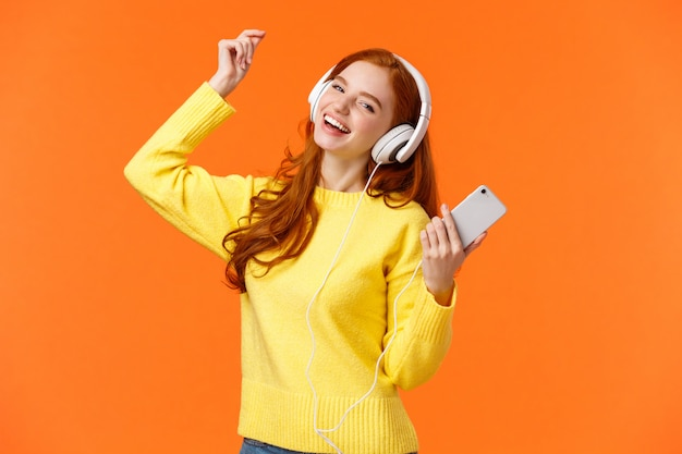 Une rousse heureuse insouciante reçoit de nouveaux écouteurs pour un cadeau de noël, danse