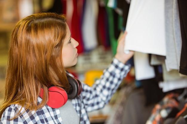 Rousse hipster regardant les vêtements