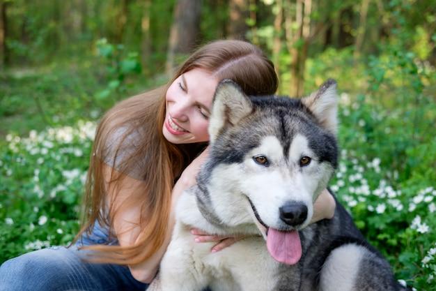 Rousse jeune femme joue avec son chien malamute sur une promenade dans la forêt