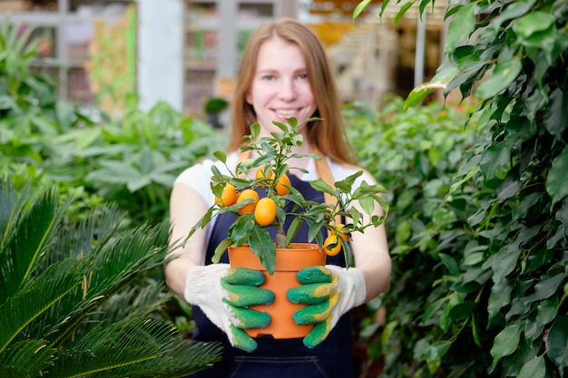 Rousse, jeune, femme, marché plante, vendeur, serre, offrir, mandarine, arbre