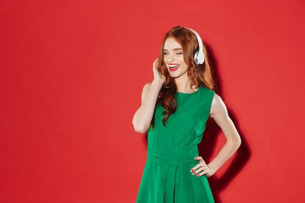 Rousse jeune fille heureuse, écouter de la musique avec des écouteurs