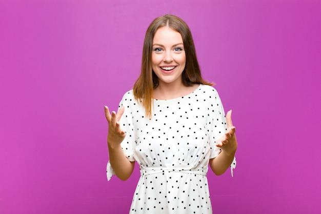 Rousse jolie femme se sentant heureuse, étonnée, chanceuse et surprise, comme dire sérieusement omg? incroyable contre le mur violet