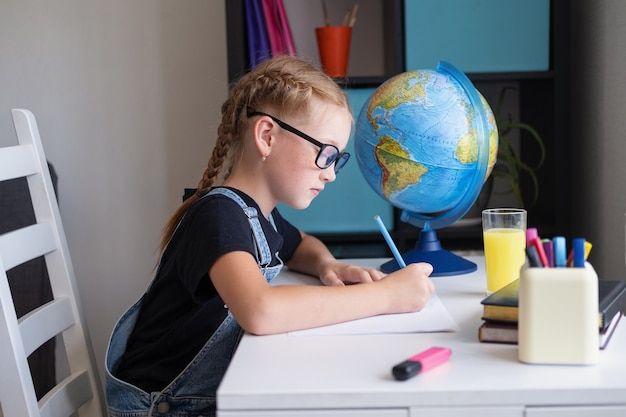 Une rousse sérieuse à lunettes étudie à la maison, fait ses devoirs. l'écriture. intello. retour à l'école