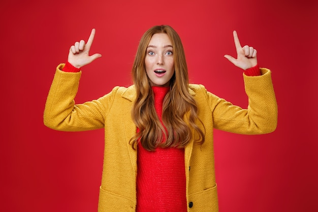 Rousse surprise en manteau jaune bouche ouverte impressionnée et ravie de lever les mains et de pointer...