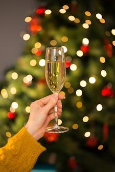 Rousse tenant un verre de champagne sur un canapé à noël