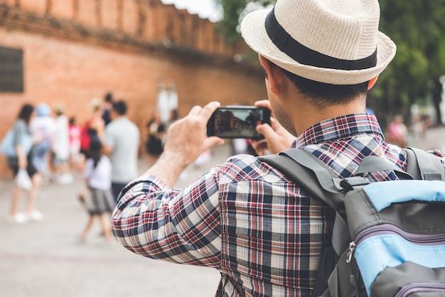 Routard mâle asiatique prenant des photos avec un smartphone à tha phae gate, l'un des anciens monuments célèbres de la ville de chiang mai, thaïlande