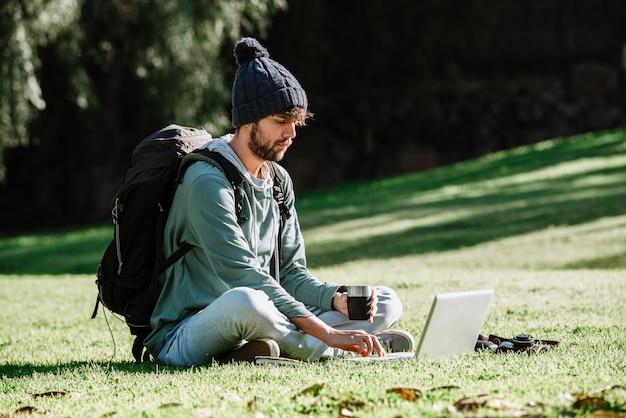 Le routard nomade numérique boit du café et travaille sur son projet indépendant.