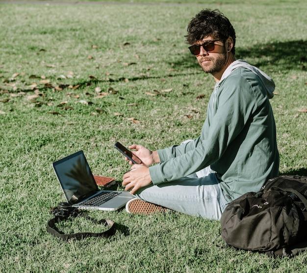 Routard nomade numérique avec ordinateur portable, appareil photo et téléphone portable, travaillant sur son projet indépendant.