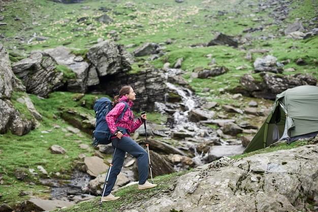 Routard sportif féminin remontant la pente rocheuse de belles montagnes brumeuses