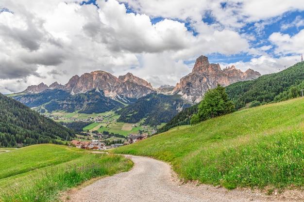 Route alpine pittoresque menant à la ville de corvara en badia et dolomites italiennes avec un pic sassongher en arrière-plan.