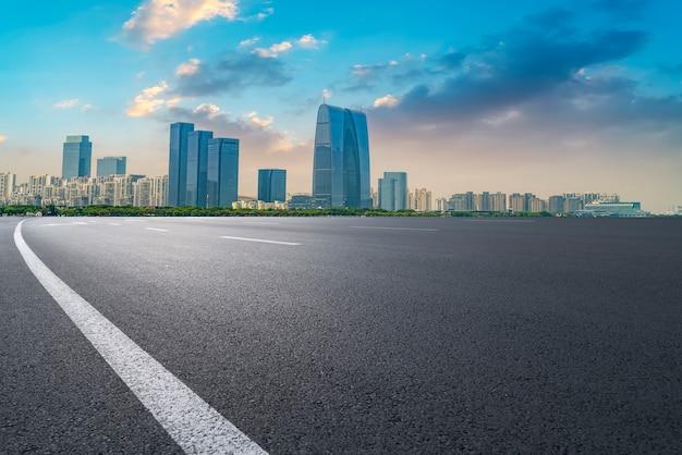 Route d'asphalte vide le long des bâtiments commerciaux modernes dans les villes de chine