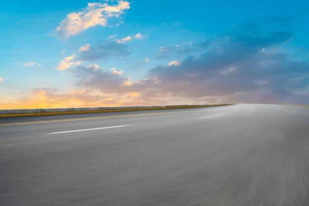 Route d'asphalte vide et paysage naturel dans le soleil couchant