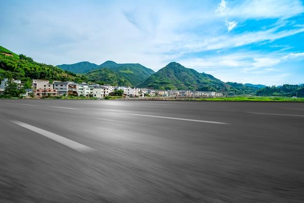 Route d'asphalte vide et paysage naturel sous le ciel bleu