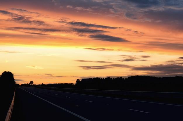Route d'asphalte vide et soleil levant sur la ligne d'horizon. coucher de soleil coloré sur la route. design de style minimaliste. fond de nature, paysage avec espace de copie.
